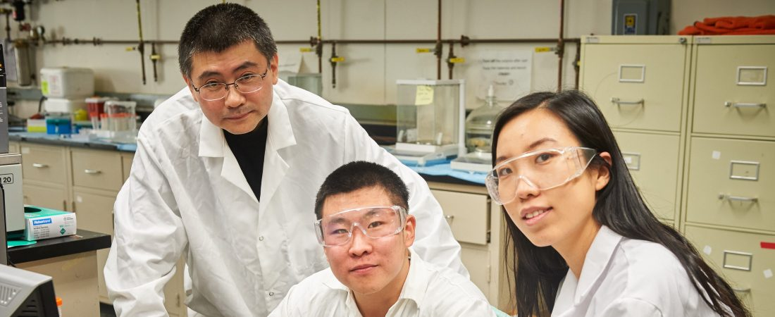 Yu Lei, associate professor of chemical & biomolecular engineering, left, with graduate students Qiuchen Dong and Xiaoyu Ma connect a toxic chemical sensor to a cable in the lab at the United Technologies Engineering Building on Feb. 2, 2016. (Peter Morenus for UConn)