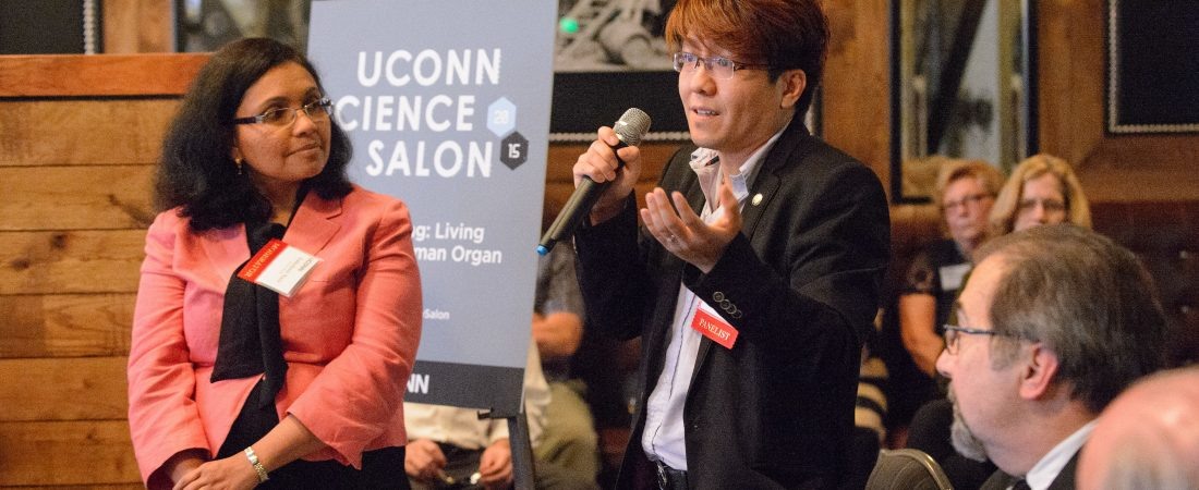 Anson Ma, center, assistant professor of chemical engineering, speaks during the UConn Science Salon held at NIXS Hartford on June 4, 2015. At left is lakshmi Nair, assistant professor of orthopedic surgery and chemical, materials and bio-molecular engineering. (Peter Morenus/UConn Photo)